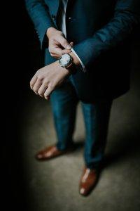 Мъж в костюм, който си оправя часовника